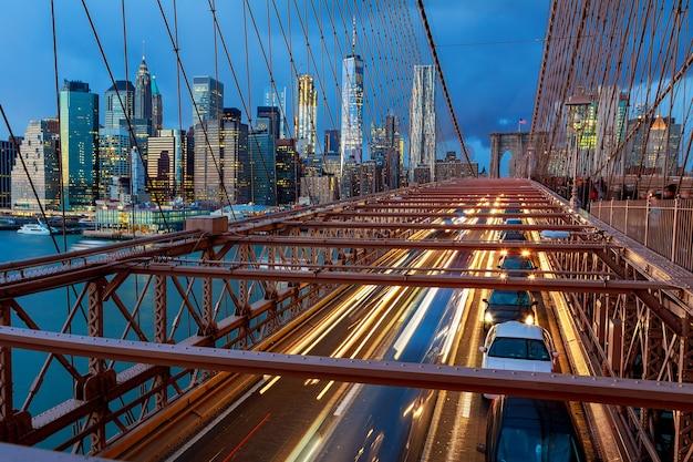Vista da ponte do brooklyn à noite com tráfego de carros noturno. ponte do brooklyn