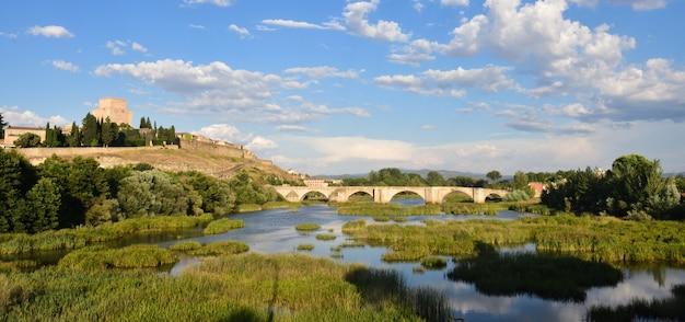 Vista da ponte e o castelo de henrique ii de castela (século xiv) e o rio agueda, ciudad rodrigo, castela e leão, espanha