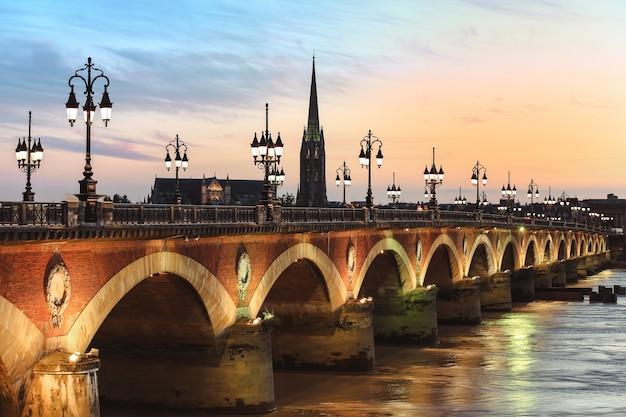 Vista da ponte pont de pierre com st michel churh em bordeaux ao pôr do sol