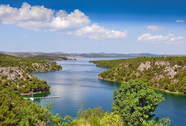 Vista da ponte sibenik para o desfiladeiro do rio krka em direção ao mar adriático. a jusante da cidade de skradin, dalmácia, croácia. imagem romântica do litoral.