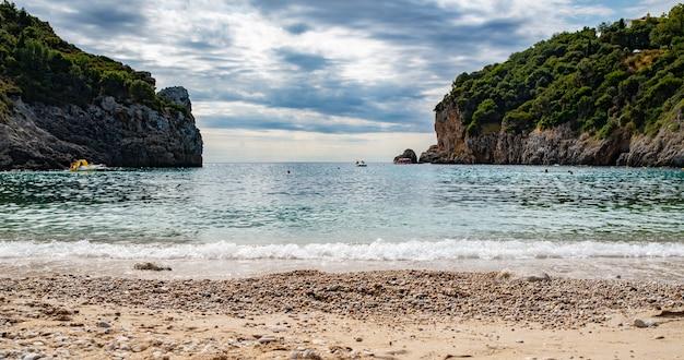 Vista da praia da incrível baía com águas cristalinas em paleokastritsa na ilha de corfu, grécia. bela paisagem de duas rochas com árvores.
