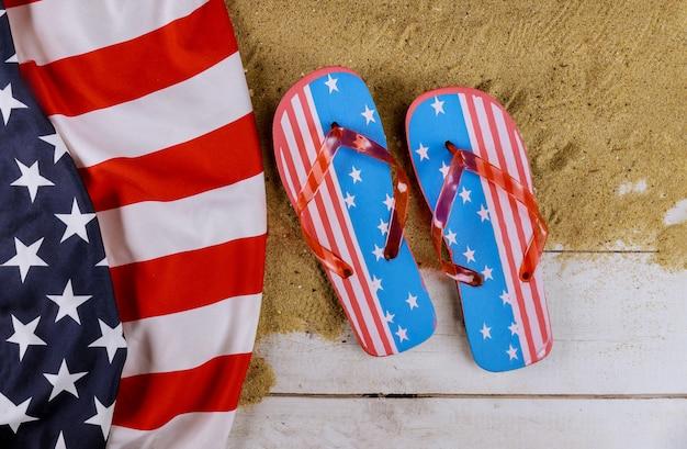 Vista da praia de areia com bandeira americana, férias de temporada de verão chinelos de praia