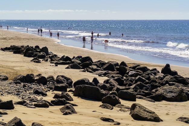 Vista da praia de maspalomas nas ilhas canárias com área dourada e pedras, pessoas caminhando ao longo da orla junto ao mar. espanha. europa.