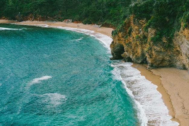 Vista da praia de mogren em budva perto do mar azul e montanhas rochosas verdes