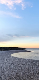 Vista da praia em liverpool ao pôr do sol, fileiras de quebra-mares, reino unido