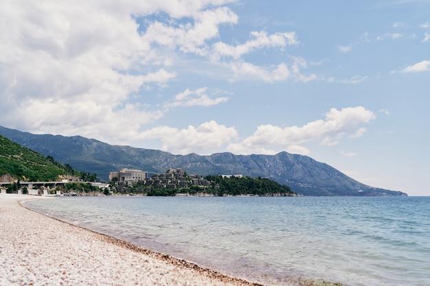 Vista da praia para a ilha das montanhas do mar e casas