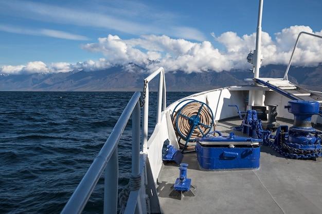 Vista da proa de um navio com a costa da montanha à frente