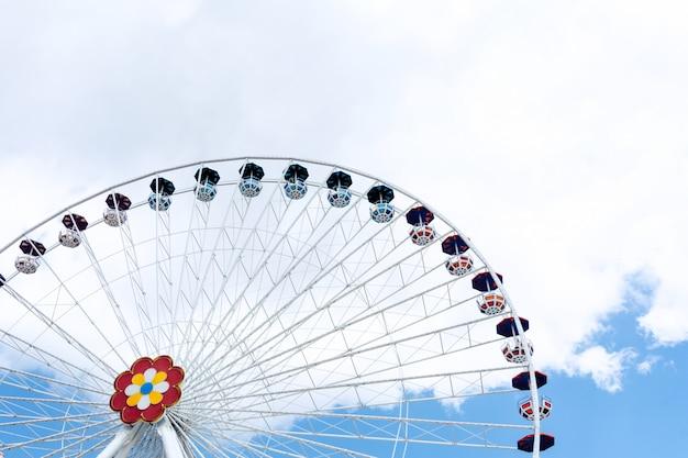Vista da roda gigante na perspectiva do céu azul e nuvens brancas.