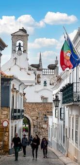 Vista da rua histórica onde se encontra o arco da vila, portão da fortaleza do século xix, faro, portugal.