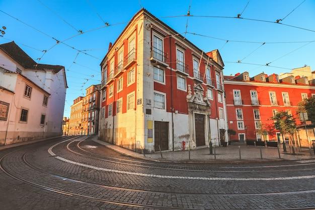 Vista da rua velha tradicional e de edifícios coloridos na manhã com as trilhas do bonde em lisboa.