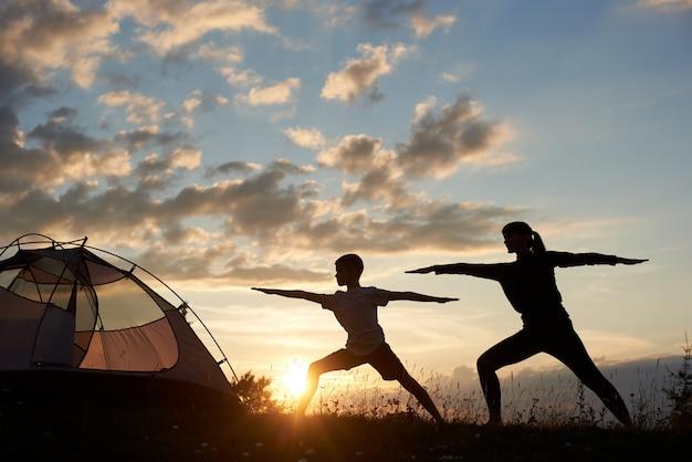 Vista da silhueta da pose de guerreiro de ioga exercitando-se com o casal perto da tenda ao amanhecer