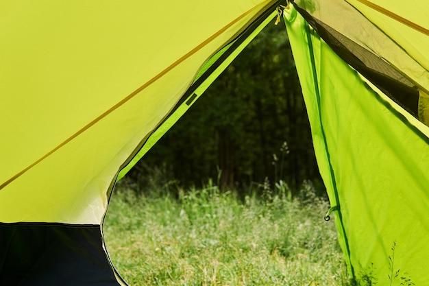 Vista da tenda de caminhada para a floresta no verão por meio de uma entrada aberta