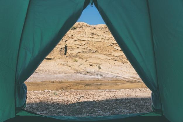 Vista da tenda do turista para o pequeno rio da montanha