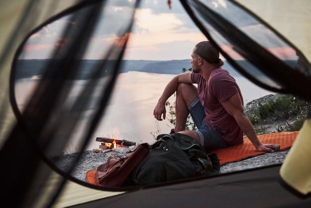 Vista da tenda do viajante com mochila sentado no topo da montanha, apreciando a vista costa de um rio ou lago.