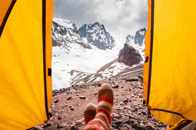 Vista da tenda para as montanhas e picos cobertos de neve, pernas femininas em meias de lã na natureza