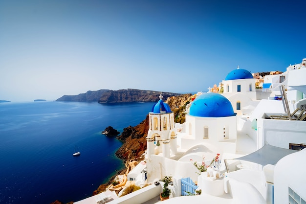 Vista da tradicional vila grega de oia de santorini, com cúpulas azuis contra o mar e a caldeira, grécia, em tons