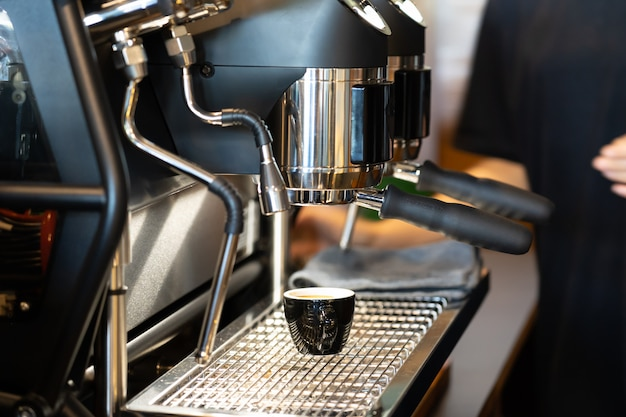 Vista da xícara de café sob moedor de café.