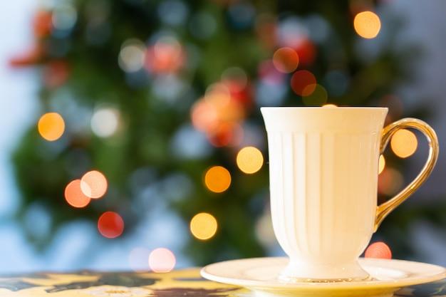 Vista da xícara de chá na mesa de madeira com luz chrismas no evento chrismas