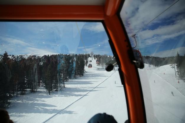 Vista das cabines de gôndola do teleférico elevador em montanhas nevadas de inverno fundo belas paisagens