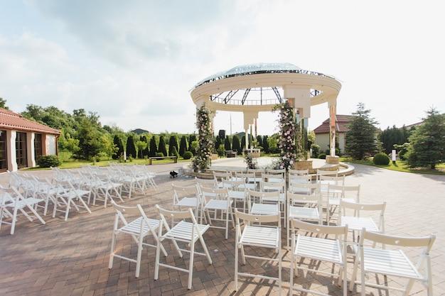 Vista das cadeiras brancas do convidado e do arco cerimonial decorado ao ar livre no dia ensolarado