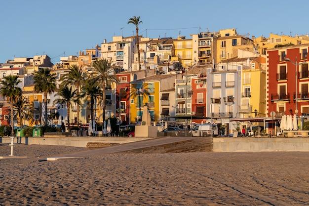Vista das casas coloridas da cidade de villajoyosa de sua praia ao nascer do sol, alicante, espanha.