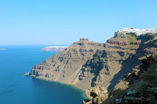 Vista das encostas e camadas de rocha vulcânica com a cidade no topo, santorini, grécia