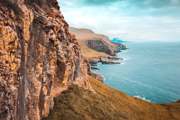 Vista das falésias e da costa no mar da ilha de mykines