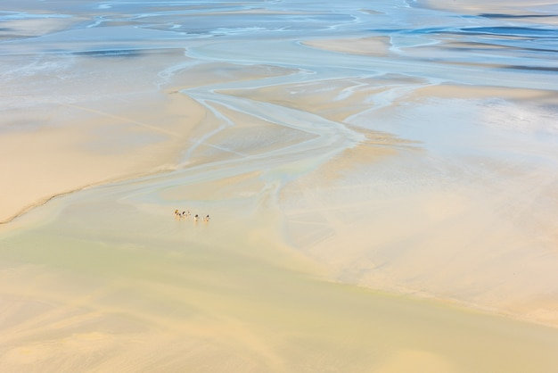 Vista das paredes do mont saint michel, na baía durante a maré baixa, com grupos de turistas caminhando. frança