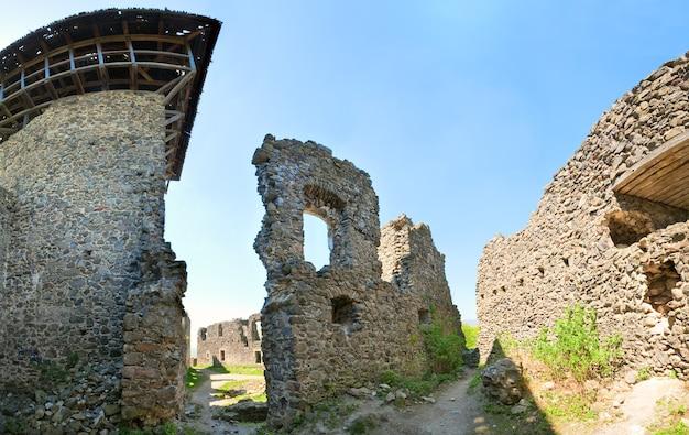 Vista das ruínas do castelo de nevytsky no verão (vila kamyanitsa, 12 km ao norte de uzhhorod, oblast de zakarpattia, ucrânia). construída no século xiii. quatro tiros costuram a imagem fazendo com lente grande angular.