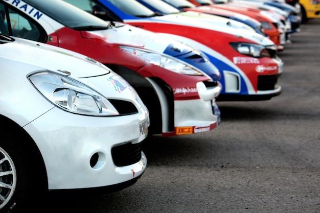 Vista de alguns carros alinhados coloridos da reunião no asfalto.