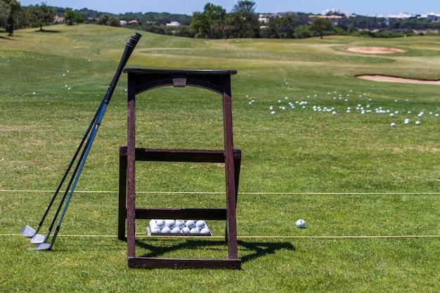 Vista de alguns clubes de golfe em um campo praticando do teste.