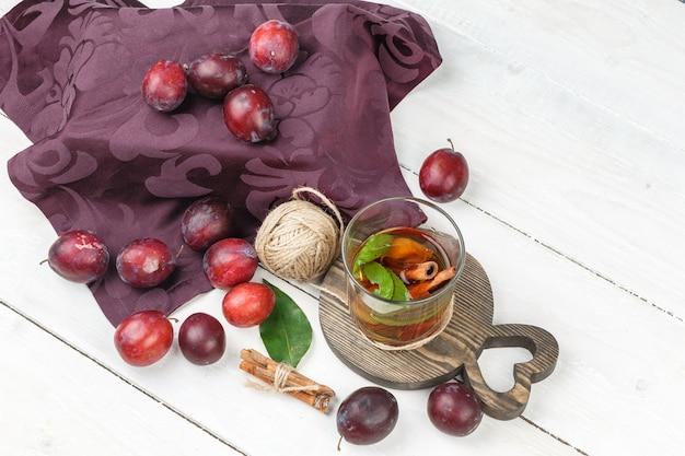 Vista de alto ângulo bebida fermentada com canela, canela e toalha de mesa cor de vinho na superfície da placa de madeira branca. horizontal