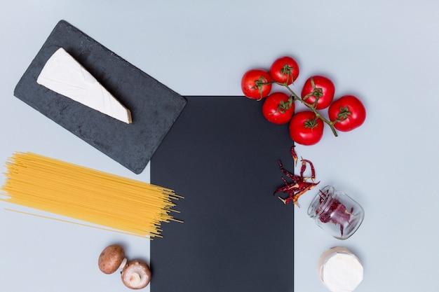 Vista de alto ângulo cru macarrão espaguete cru e é ingrediente com pedra ardósia