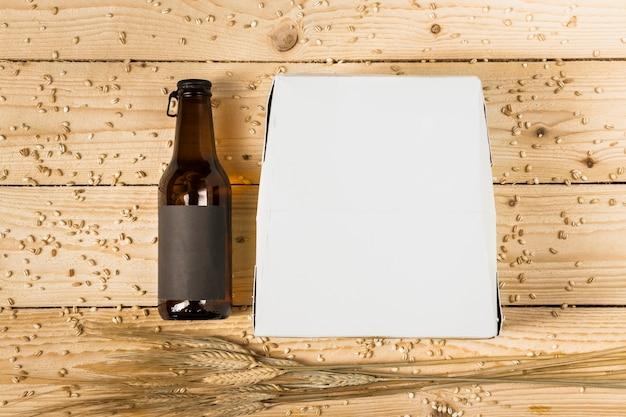 Vista de alto ângulo da caixa de papelão; garrafa de cerveja e espigas de trigo na prancha de madeira