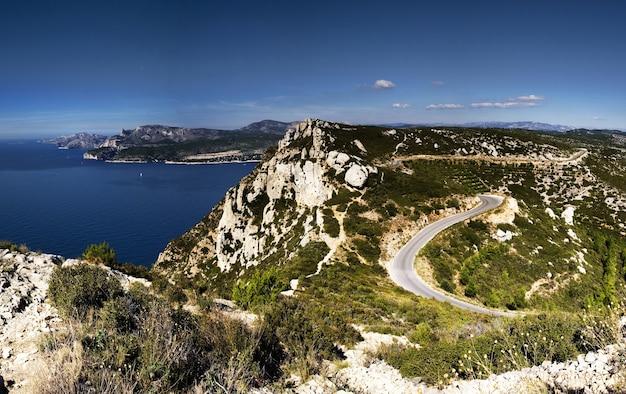 Vista de alto ângulo da corniche des cretes cercada por vegetação e o mar na frança