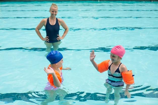 Vista de alto ângulo da instrutora e meninas na piscina