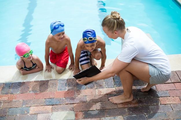 Vista de alto ângulo da instrutora mostrando a prancheta para as crianças ao lado da piscina