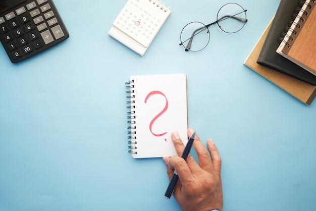 Vista de alto ângulo da mão desenhando um ponto de interrogação no papel na mesa do escritório