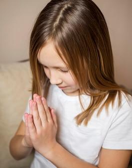 Vista de alto ângulo da menina rezando