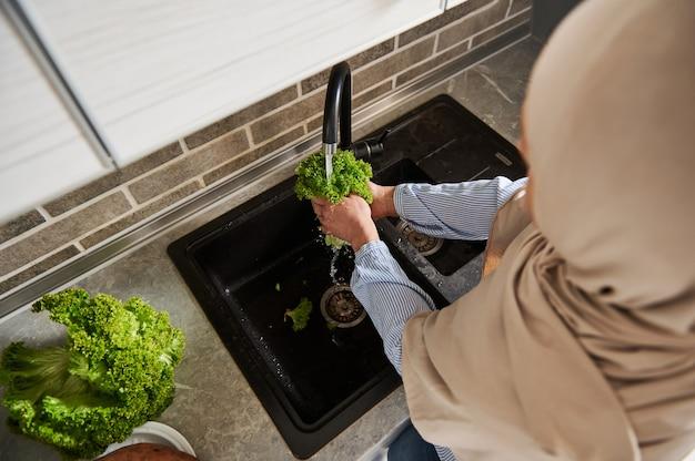 Vista de alto ângulo da mulher árabe muçulmana em hijab lavando salada de folhas em pé na cozinha. fechar-se