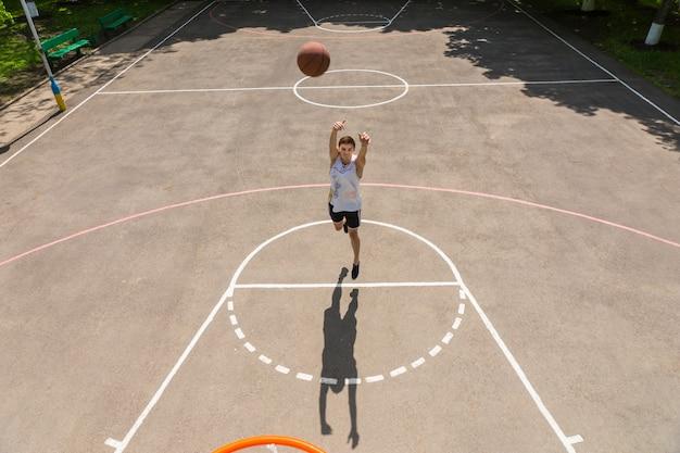 Vista de alto ângulo da tabela de um jovem atlético atirando na linha de lance livre na tecla da quadra de basquete ao ar livre em dia ensolarado