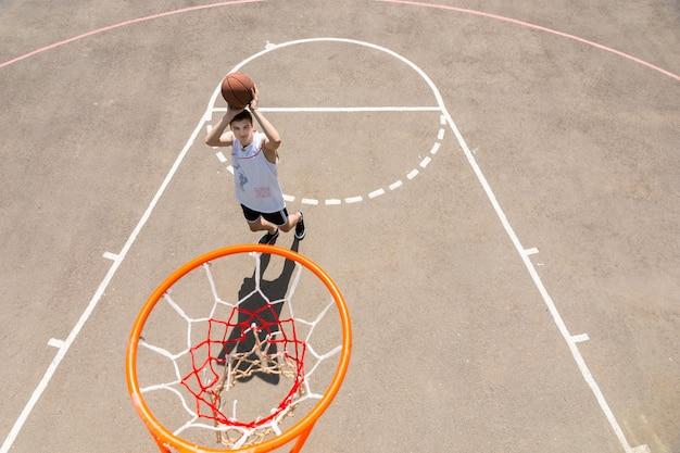 Vista de alto ângulo da tabela do jovem atlético atirando na rede na quadra de basquete ao ar livre