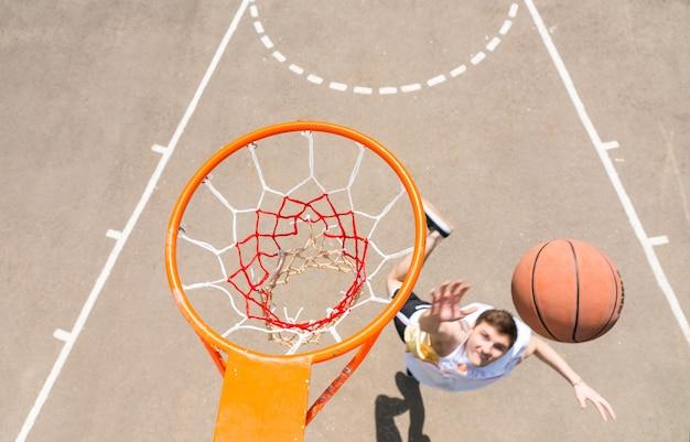 Vista de alto ângulo da tabela do jovem atlético fazendo lay-up, tiro na rede, na quadra de basquete ao ar livre