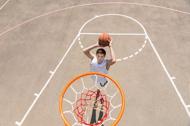 Vista de alto ângulo da tabela do jovem atlético fazendo um arremesso na rede na quadra de basquete ao ar livre