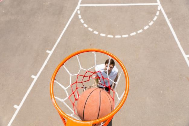 Vista de alto ângulo da tabela do jovem atlético fazendo um tiro na rede na quadra de basquete ao ar livre em um dia ensolarado