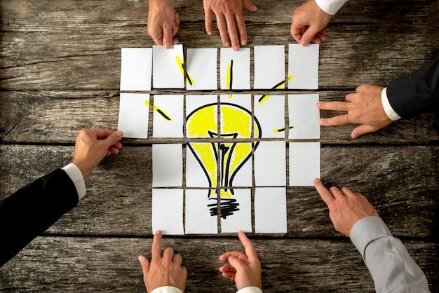 Vista de alto ângulo das mãos de empresários tocando documentos brancos dispostos em uma mesa de madeira rústica, formando uma lâmpada amarela