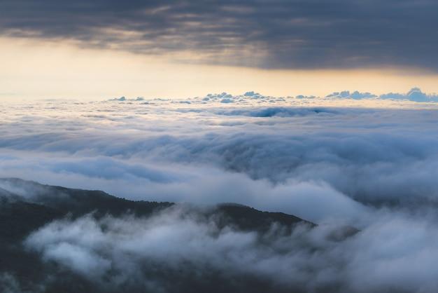 Vista de alto ângulo das nuvens sobre as colinas ao pôr do sol