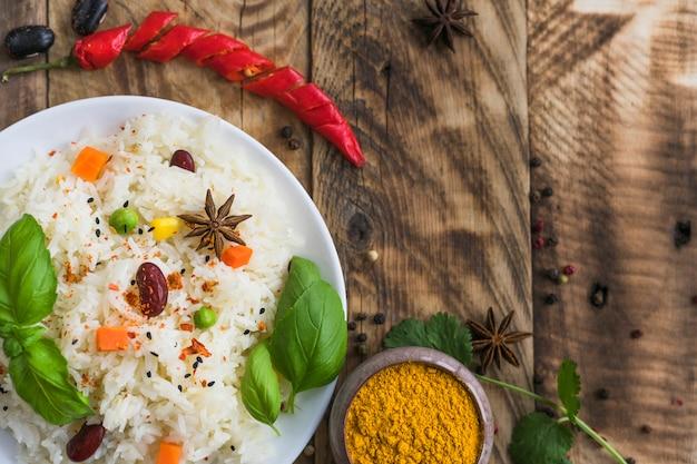 Vista de alto ângulo de arroz vegetal; açafrão em pó; pimenta vermelha e especiarias secas sobre o pano de fundo de madeira