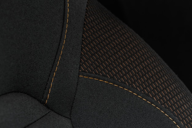 Vista de alto ângulo de bancos de tecido de automóveis modernos. textura do assento do carro do close-up e detalhes do interior. imagem detalhada de um trabalho de ponto de pregas de carro.
