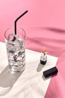 Vista de alto ângulo de batom e copo com gelo na mesa de fundo branco e rosa com sombra.